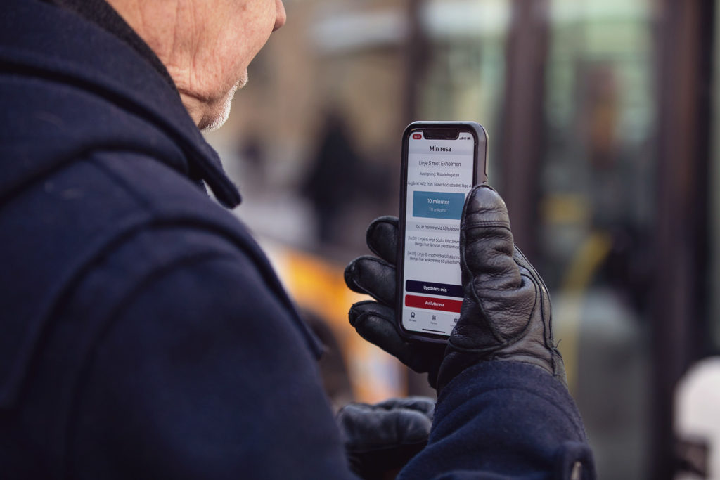 En person håller i en telefon med appen digital ledsagning framför sig